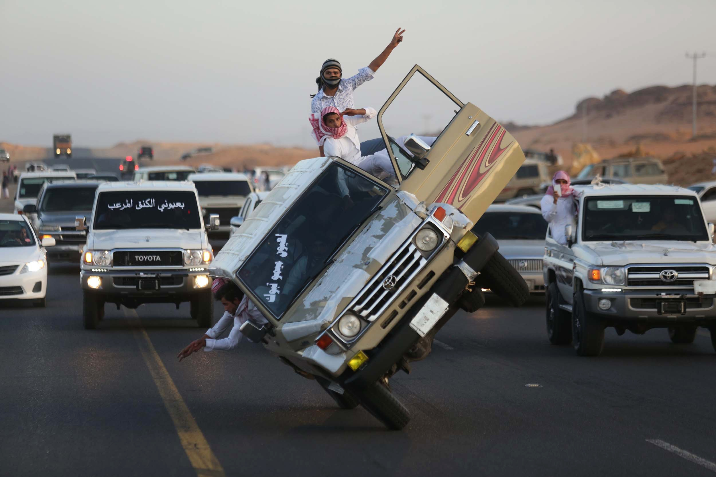 """Saudi youths demonstrate a stunt known as """"sidewall skiing"""" (driving on two wheels) in the northern city of Tabuk"""
