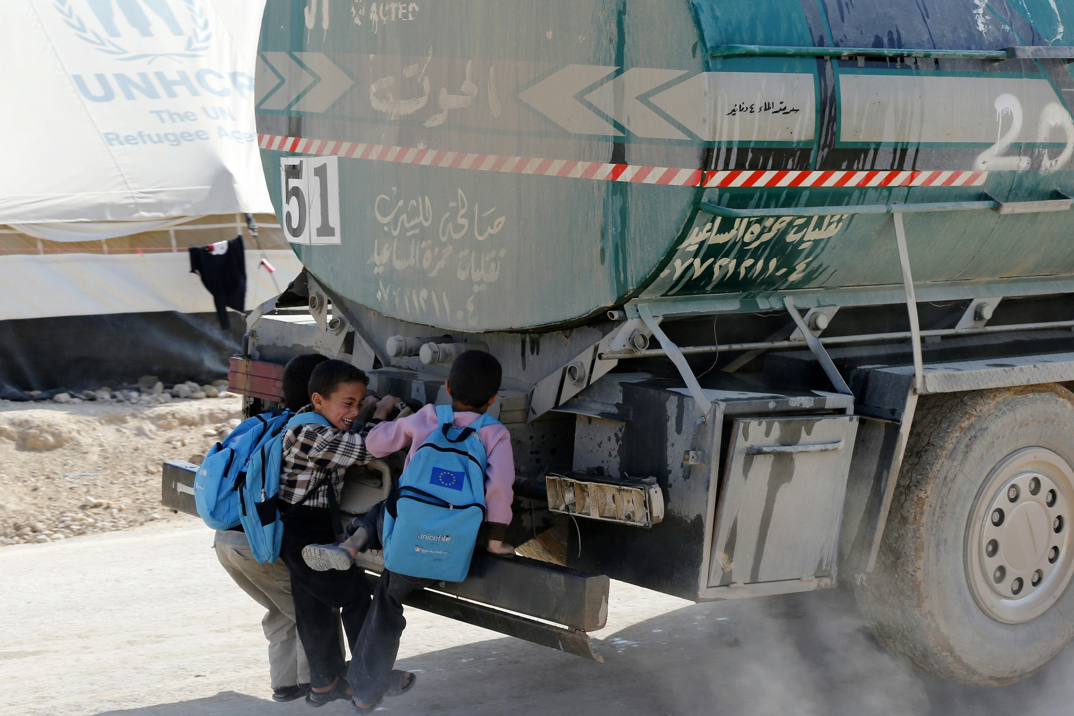 Syrian children hitch a ride from the back of a water tanker at the Al Zaatari refugee camp in the Jordanian city of Mafraq, near the border with Syria
