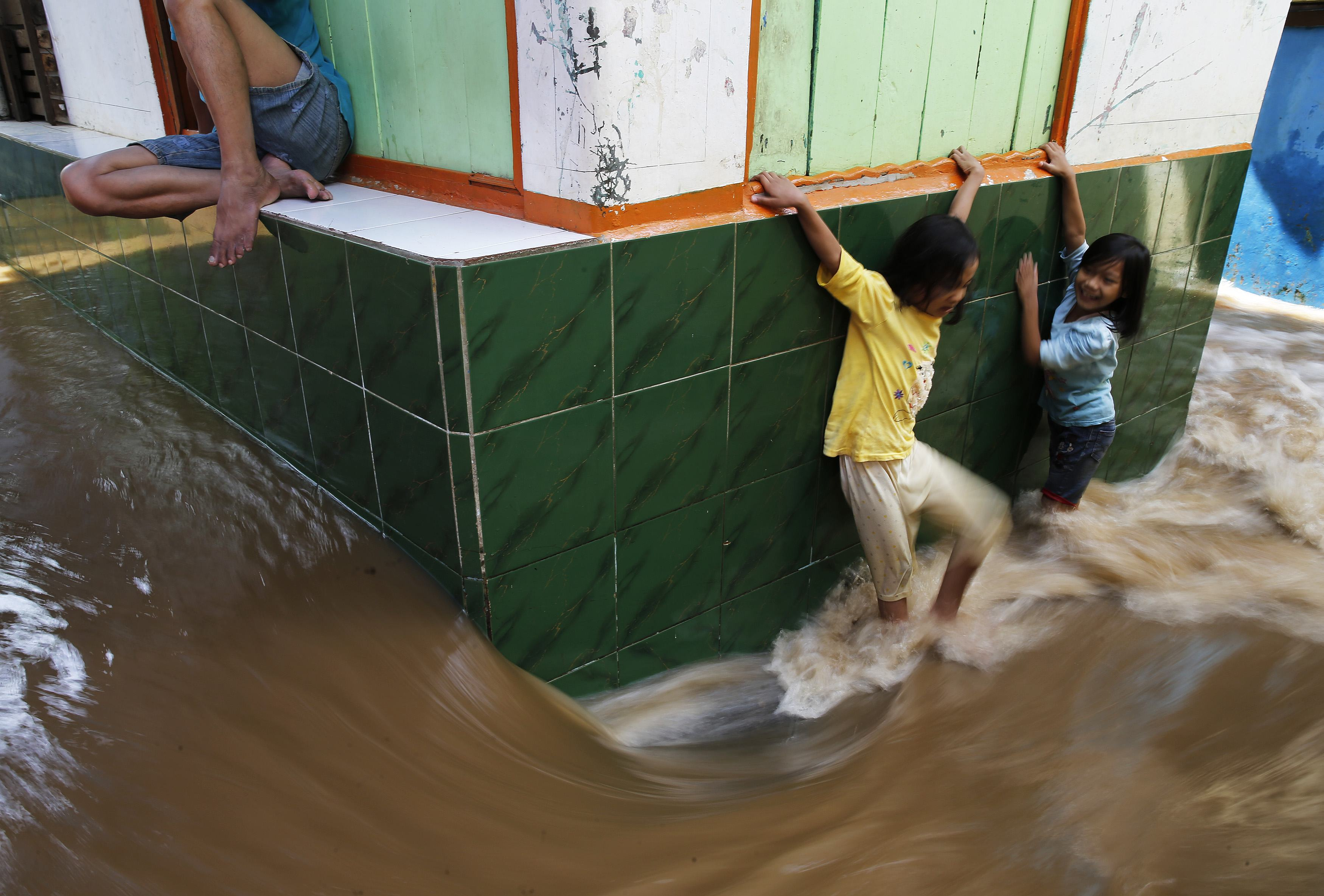 Children try to walk through a flooded street at Kampung Melayu residential area in Jakarta