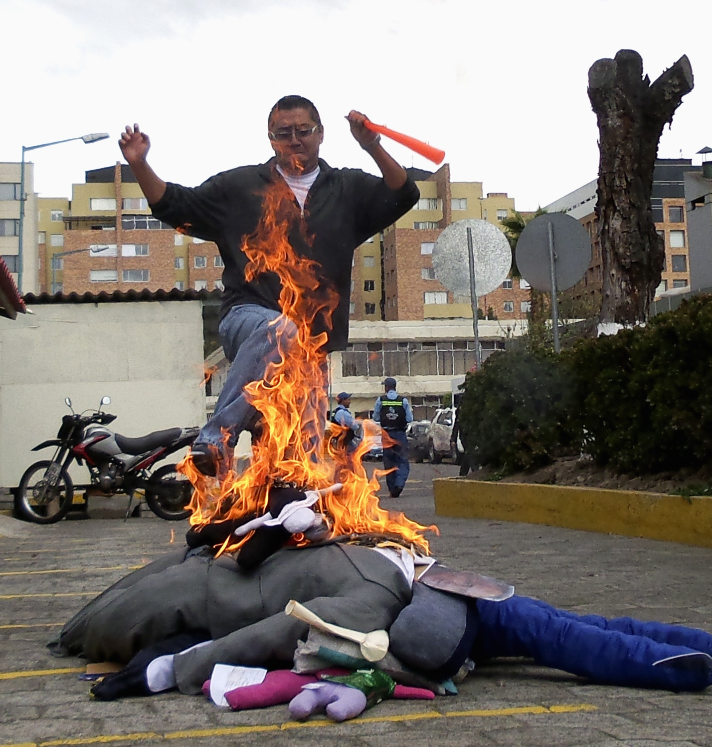Revelers burn a pile of handmade puppets to kick and jump over, on the streets of Quito