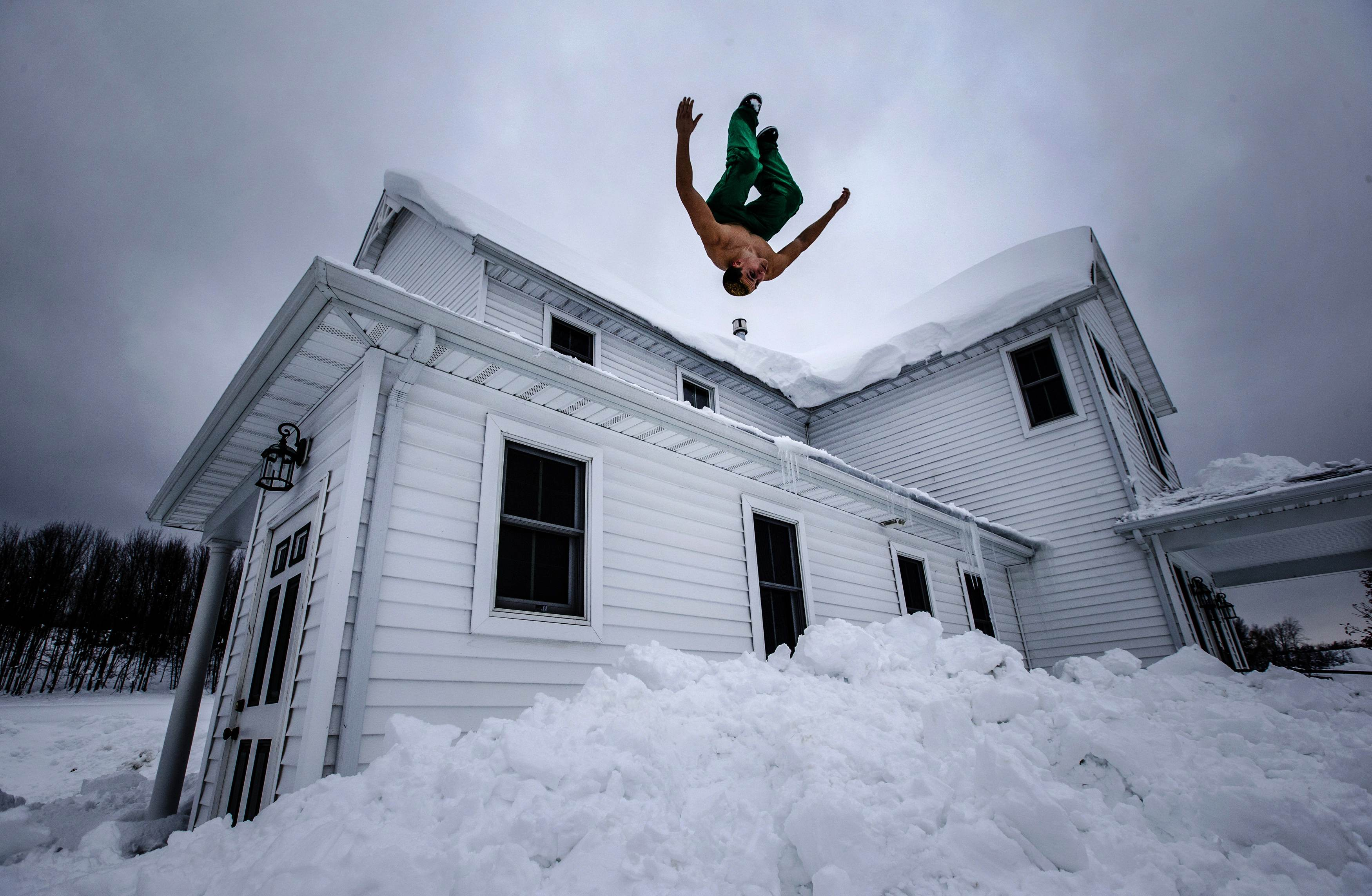 Phil Mohun does a back flip off of his family home after clearing snow from the roof following a massive snowstorm in Cowlesville