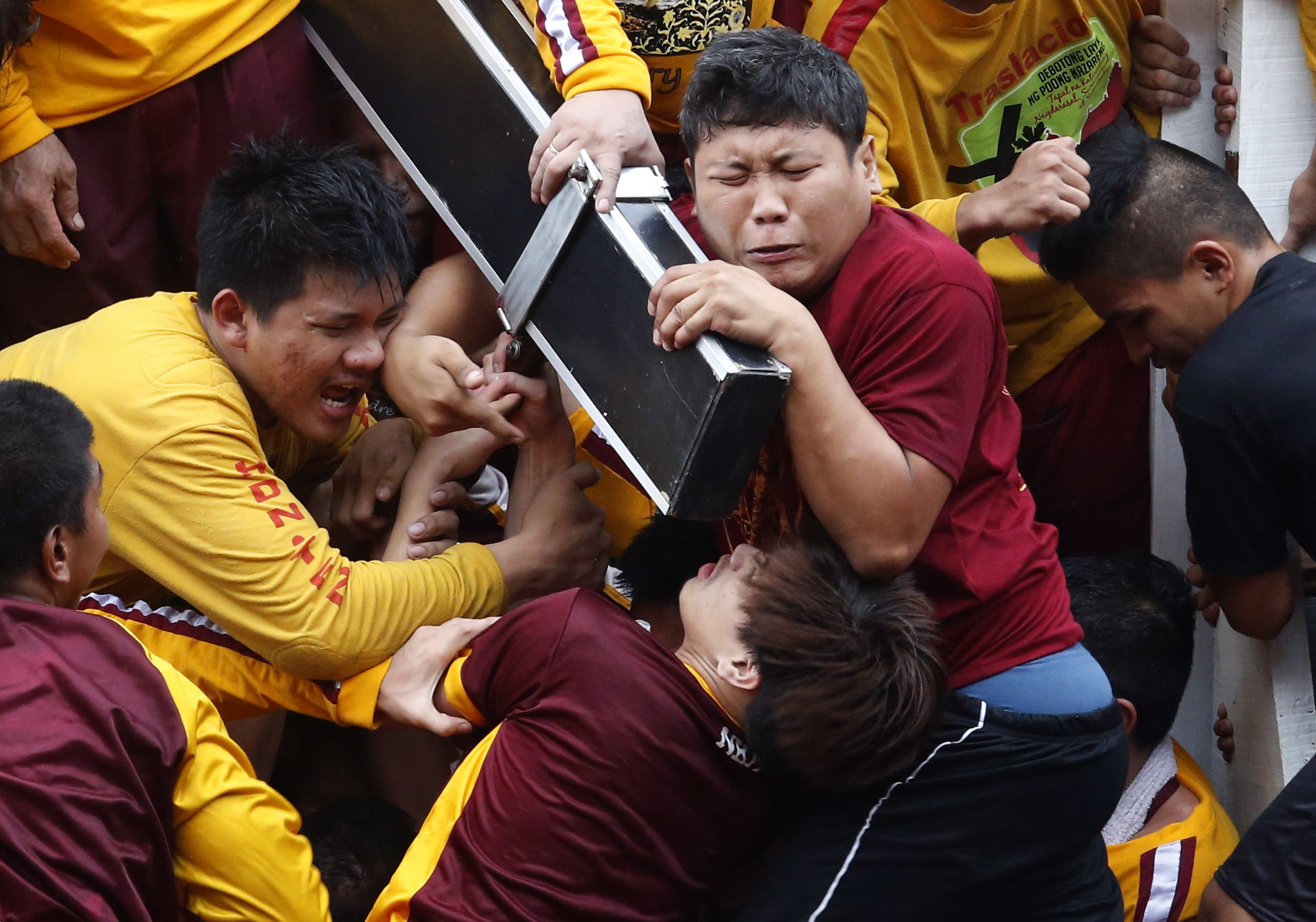 Devotees grimace as they try to hold the Black Nazarene, which is atop a carriage, at the start of an annual procession in Manila