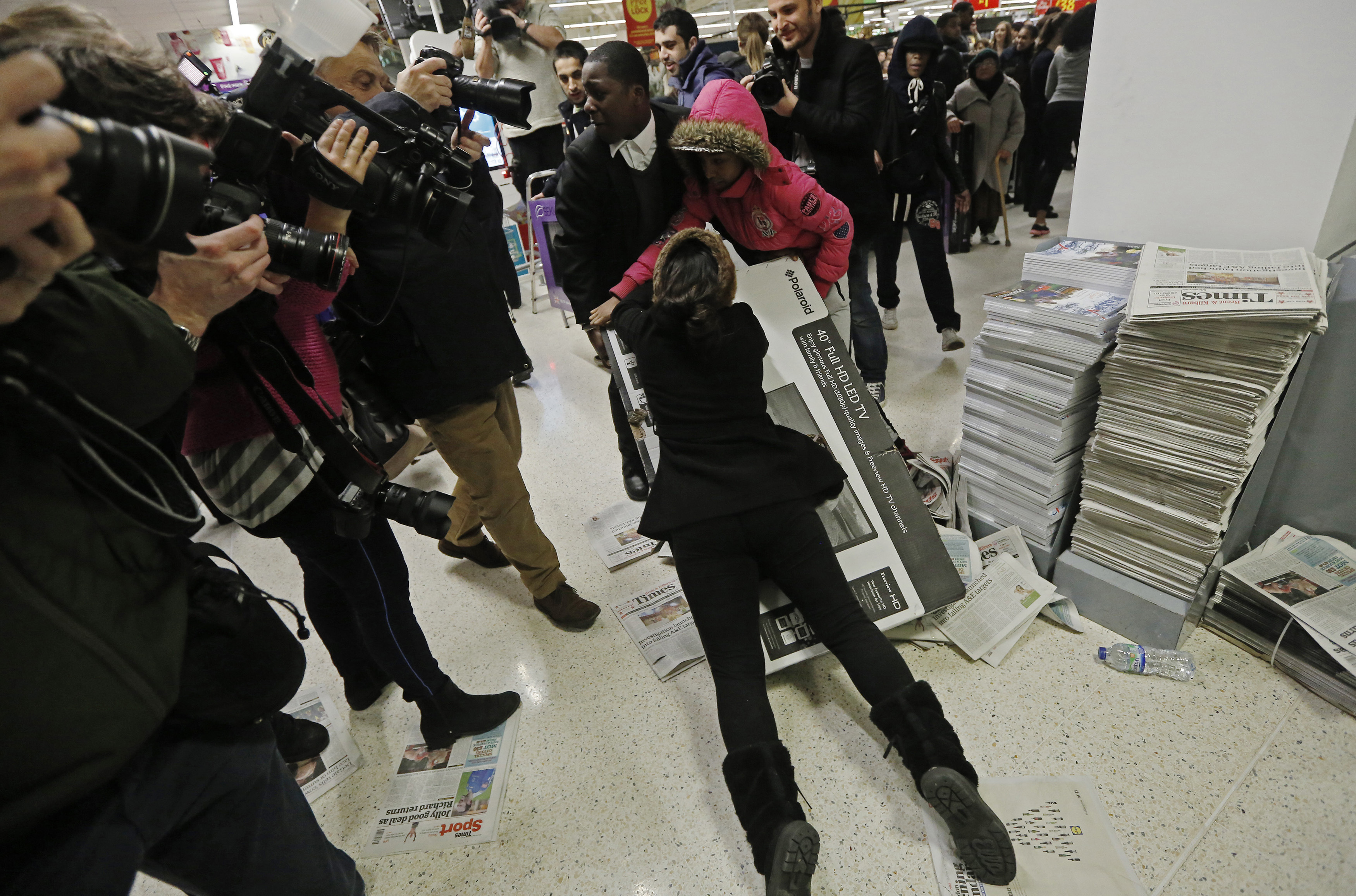 """Shoppers wrestle over a television as they compete to purchase retail items on """"Black Friday"""" at an Asda superstore in Wembley"""